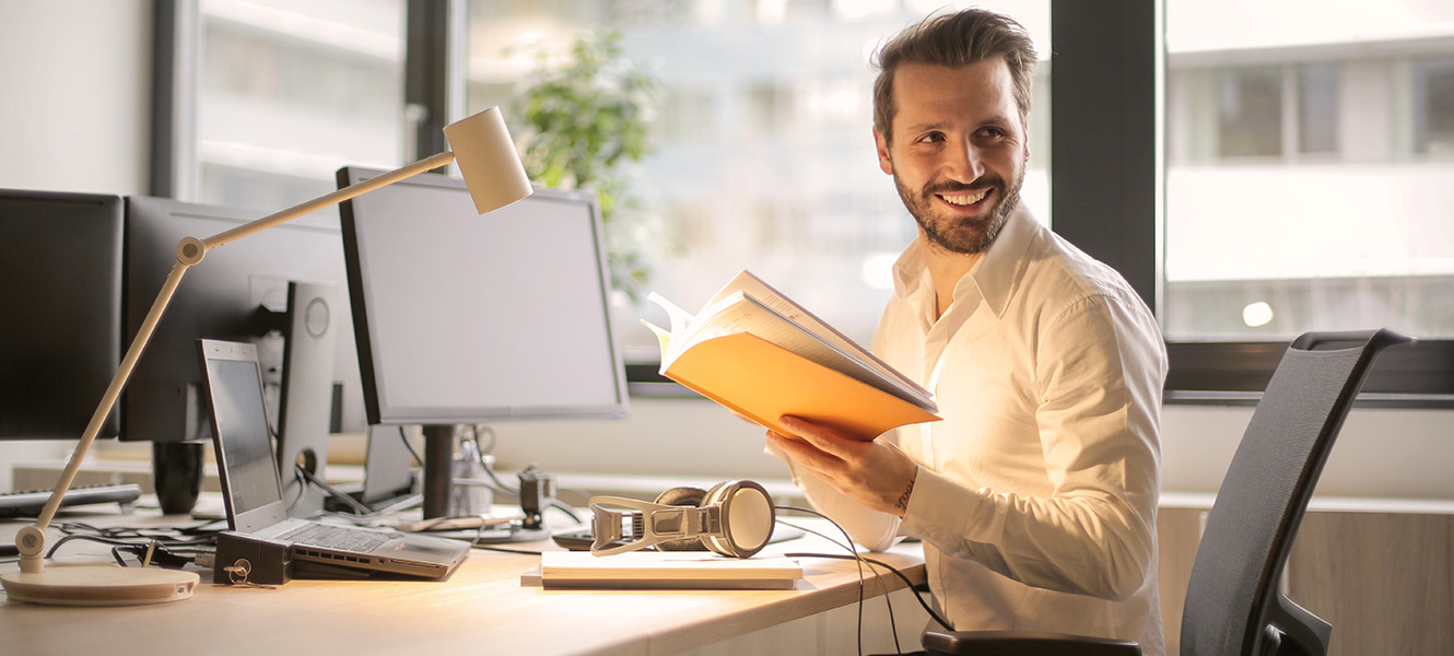 Man holding book at desk