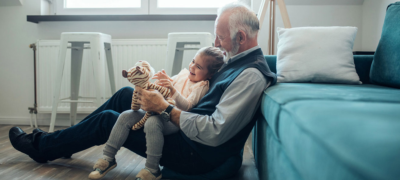 elderly man and child playing with stuffed animal