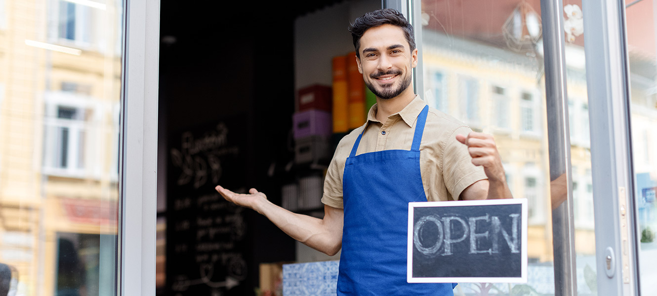 Man holding open sign outside store